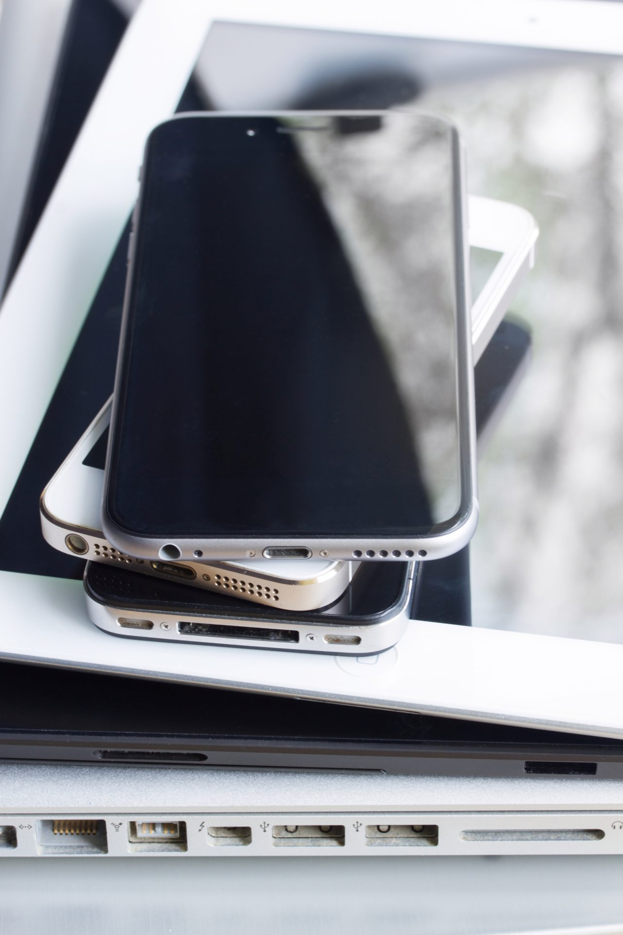 stack of modern electronical devices close up - technology concept